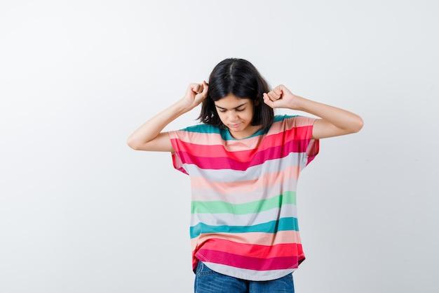 Jong meisje dat winnaargebaar toont in kleurrijk gestreept t-shirt en er serieus uitziet, vooraanzicht.