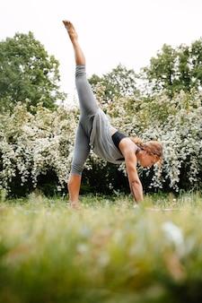 Jong meisje dat yoga beoefent op de natuur in het park van groene bomen en gras, ze balanceert op één been vrouwelijke atleet die staat