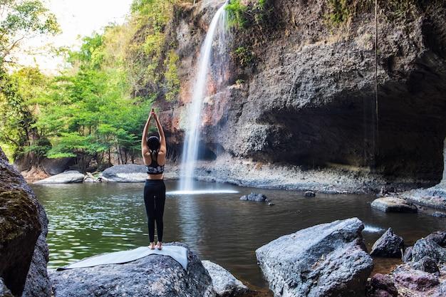 Jong meisje dat yoga doet dichtbij een waterval Premium Foto