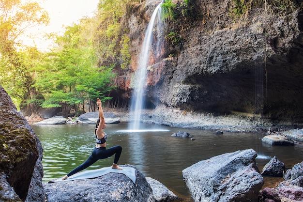 Jong meisje dat yoga doet dichtbij een waterval