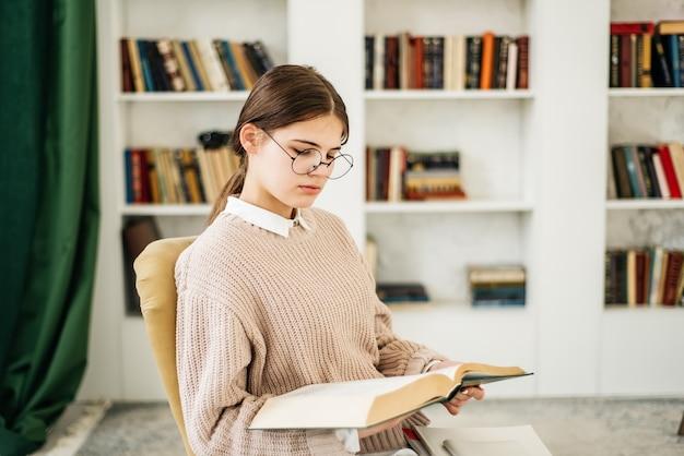 Jong meisje dat zich dichtbij de boekenplank in bibliotheek bevindt