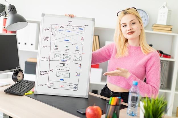 Jong meisje dat zich in het kantoor bevindt en een magnetische raad houdt.