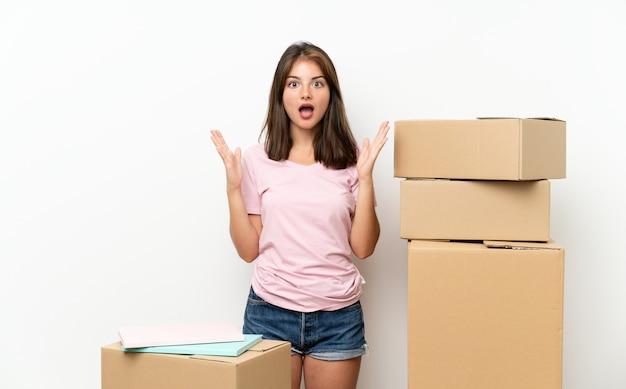 Jong meisje dat zich in nieuw huis onder dozen met verrassingsgelaatsuitdrukking beweegt