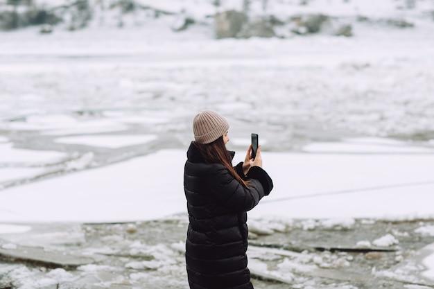 Jong meisje dat zich op de oever van de rivier bevindt die met ijsschotsen wordt bedekt en foto neemt bij het noordse landschap.