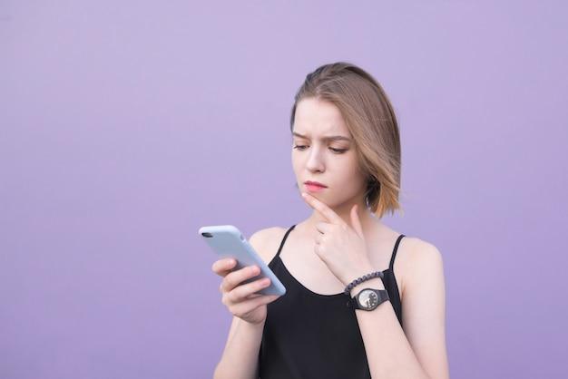 Jong meisje dat zich op een purpere achtergrond bevindt en een smartphone bekijkt