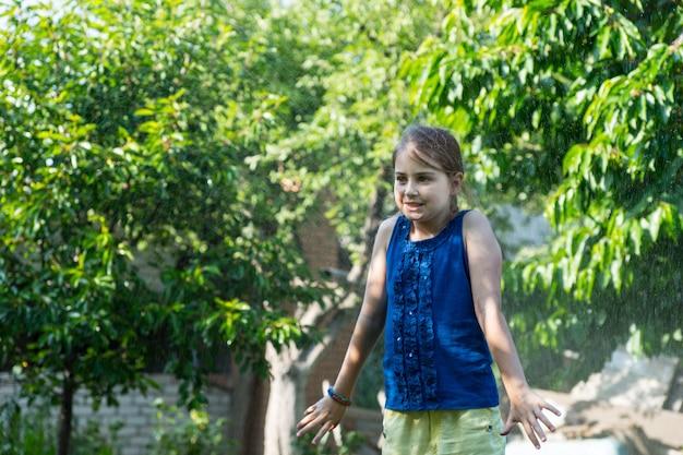 Jong meisje dat zomerkleren draagt en afkoelt in sprinkler op warme zomerdag, verrast door waternevel op de rug