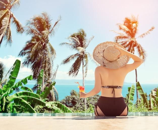 Jong meisje dat zonhoed draagt die bij de pool met cocktail situeert