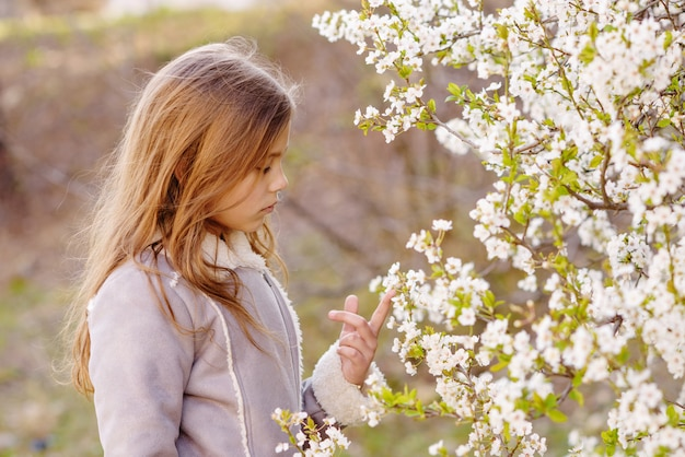 Jong meisje dichtbij bloeiende kersenboom