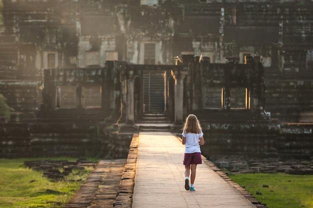 Jong meisje die aan de ruïnes van de verloren stad in zonsondergang lichte oerwouden weggaan