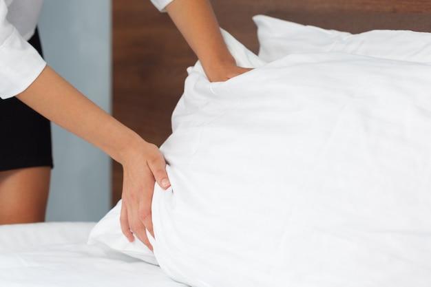 Jong meisje die bed in hotelruimte maken