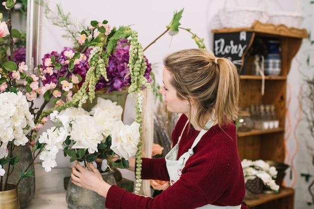 Jong meisje die bloeiende bloemen samenstellen