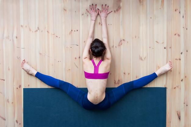 Jong meisje die brede gezette voorwaartse kromming of upavistha konasana uitvoeren tijdens het uitrekken van klasse in gymnastiek