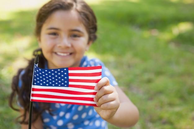 Jong meisje die de amerikaanse vlag houden bij park