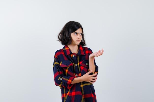 Jong meisje die de hand uitrekt als iets vast te houden terwijl ze de hand op de elleboog houdt in een geruit overhemd en er schattig uitziet, vooraanzicht.