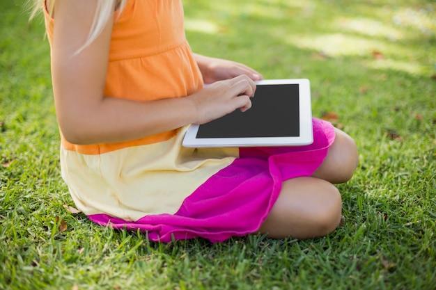 Jong meisje die digitale tablet in park gebruiken