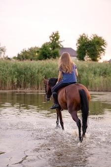 Jong meisje die een paard berijden op een ondiep meer