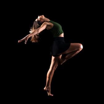 Jong meisje die en in studio op geïsoleerde achtergrond dansen springen