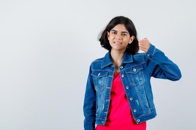 Jong meisje die hand naar camera in rood t-shirt en jeansjasje uitrekt en optimistisch kijkt. vooraanzicht.
