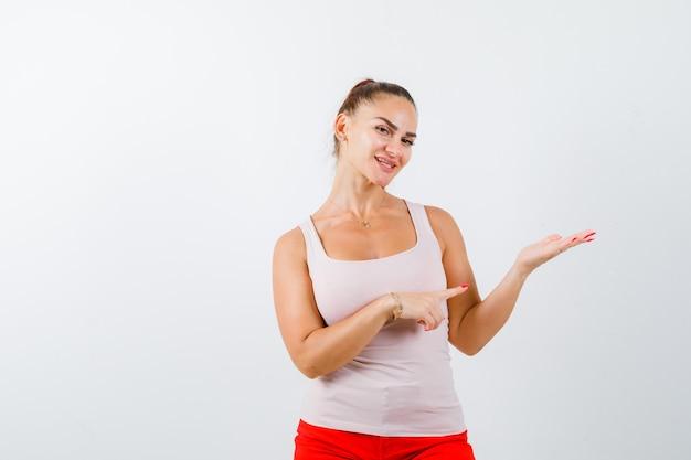 Jong meisje die hand uitrekt als iets denkbeeldigs vasthoudt en ernaar wijst in beige top en rode broek en er zelfverzekerd uitziet. vooraanzicht.