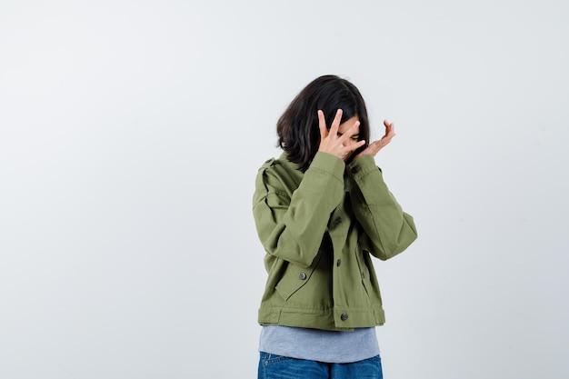 Jong meisje die handen op een boze manier uitrekt in grijze trui, kaki jas, spijkerbroek en er uitgeput uitziet. vooraanzicht.