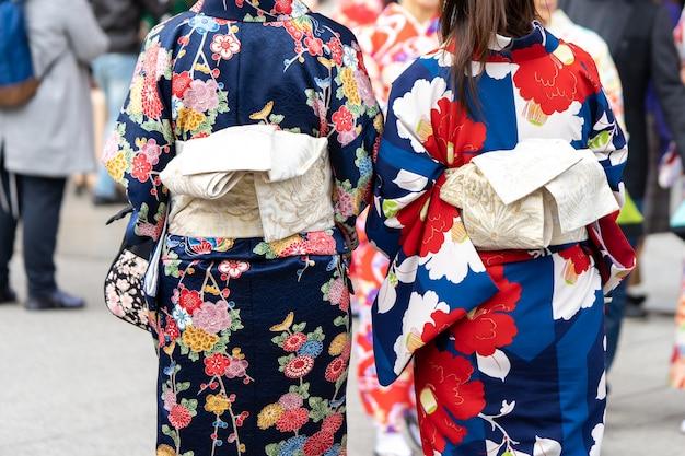 Jong meisje die japanse kimono dragen die zich voor sensoji-tempel in tokyo bevinden