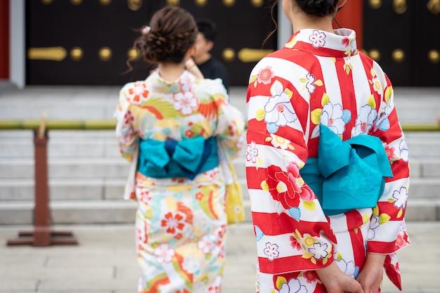 Jong meisje die japanse kimono dragen die zich voor sensoji-tempel in tokyo bevinden,