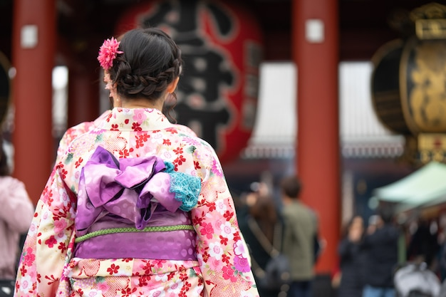Jong meisje die japanse kimono dragen die zich voor sensoji-tempel in tokyo, japan bevinden.