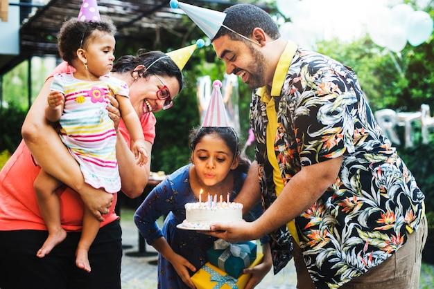Jong meisje die kaarsen blazen van haar verjaardagscake