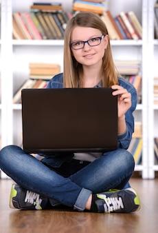 Jong meisje die laptop in de bibliotheek met behulp van.