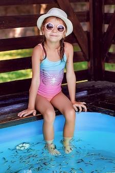 Jong meisje die massage met kleine vissen ontvangen. schillen met vis. meisje dat van geneeskrachtige procedure geniet. voetmassage met vissen in aquariumclose-up. fish spa procedure.