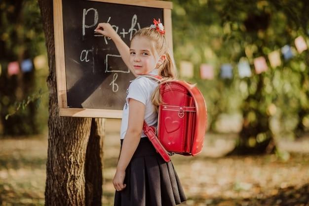 Jong meisje die met rode schooltas op een formule van raadswiskunde schrijven in een park