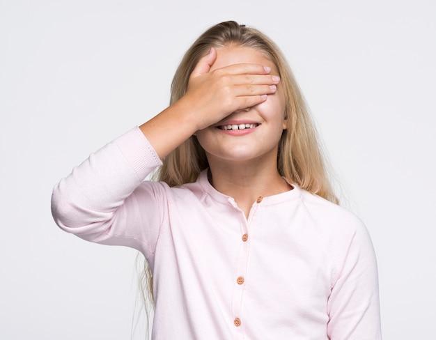 Jong meisje die ogen behandelen met hand
