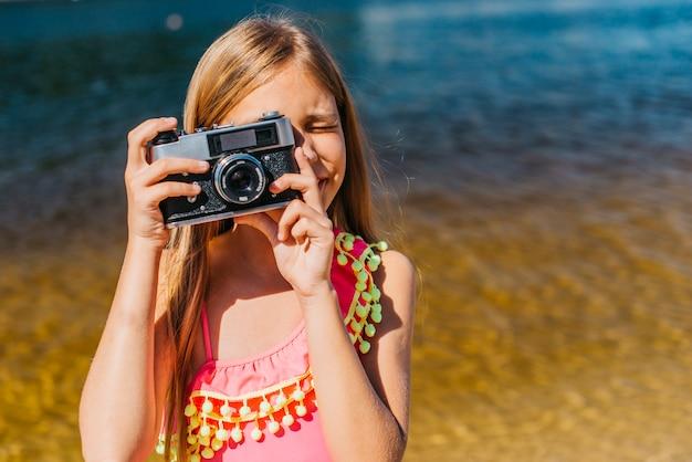 Jong meisje die op camera tegen achtergrond van overzees schieten
