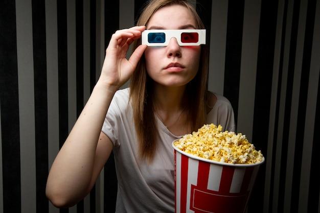 Jong meisje die op een film letten en popcorn eten