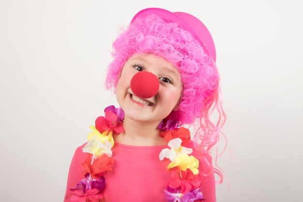 Jong meisje die pruik en clownglazen dragen en voor carnaval glimlachen