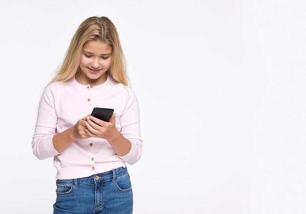 Jong meisje die telefoon met exemplaar-ruimte met behulp van