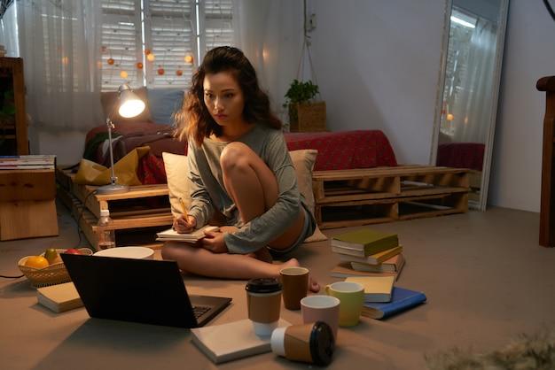 Jong meisje die voor examen voorbereidingen gezet op de vloer van haar slaapzaal die door laptop, boeken en lege koppen wordt omringd