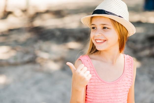 Jong meisje die weg met duim op strand richten