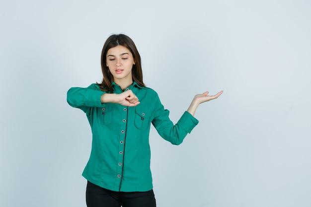 Jong meisje doet alsof ze horloge om haar pols kijkt, palm opzij spreidt in groene blouse, zwarte broek en gefocust kijkt, vooraanzicht.