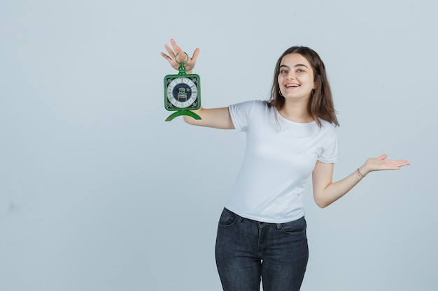 Jong meisje doet alsof ze iets laat zien terwijl ze de klok in t-shirt, spijkerbroek vasthoudt en er gelukkig uitziet. vooraanzicht.