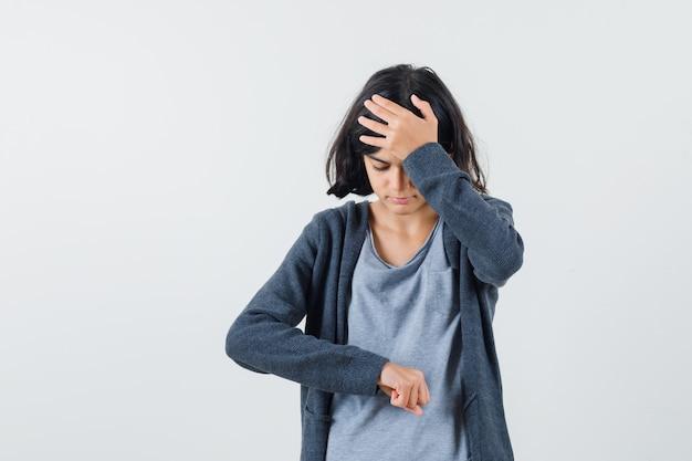 Jong meisje doet alsof ze naar de klok kijkt terwijl ze de hand op het voorhoofd legt in een lichtgrijs t-shirt en een donkergrijze hoodie met ritssluiting en er gestrest uitziet