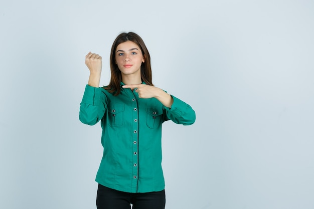 Jong meisje doet alsof ze op horloge om haar pols in groene blouse, zwarte broek wijst en gelukkig, vooraanzicht kijkt.