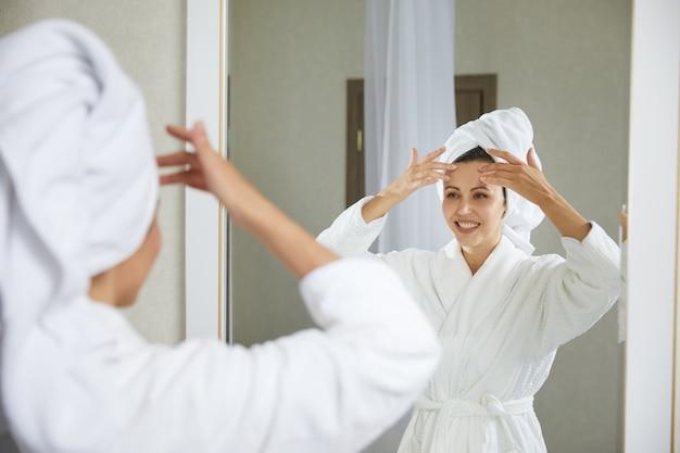 Jong meisje doet gezichtsgymnastiek zelfmassage en verjongende oefeningen in de ochtend erna