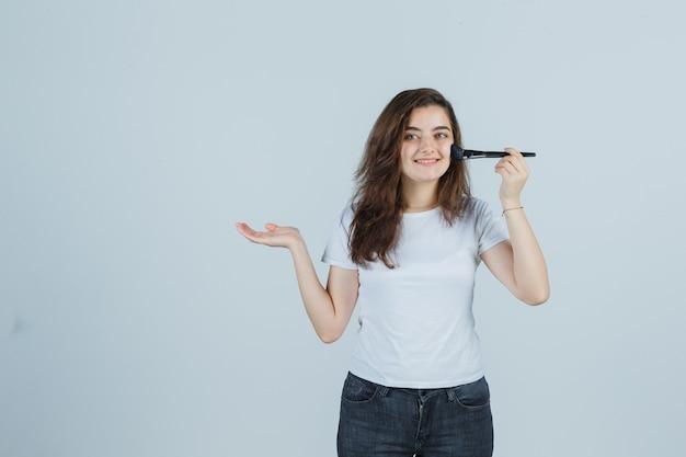 Jong meisje doet make-up met borstel terwijl ze doet alsof ze iets in t-shirt, spijkerbroek laat zien en er vrolijk uitziet. vooraanzicht.