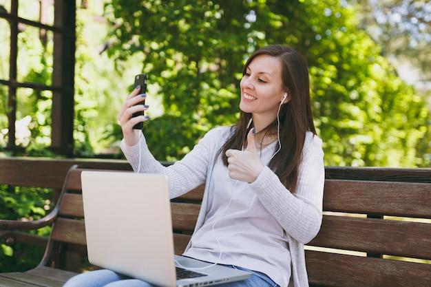 Jong meisje doet selfie op mobiele telefoon of video-oproep. vrouw zittend op een bankje bezig met moderne laptop pc-computer in stadspark in straat buiten op de natuur. mobiel kantoor. freelance bedrijfsconcept.