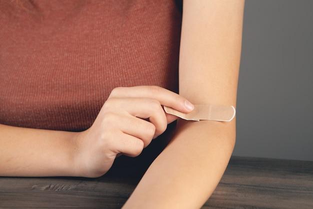 Jong meisje doet verband om haar arm