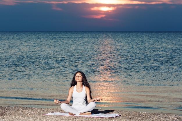 Jong meisje doet yoga of meditatie bij zonsopgang op het strand