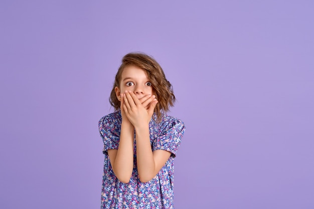 Jong meisje draagt een jurk met bloemenprint op een paarse geschokte kegelvormige mond met hand