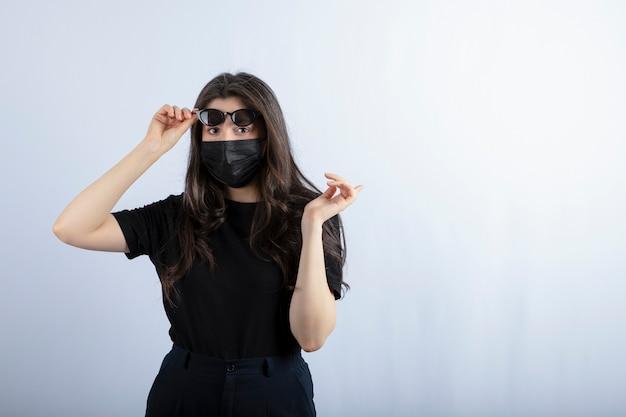 Jong meisje draagt een zwart masker vanwege de pandemie en poseren.