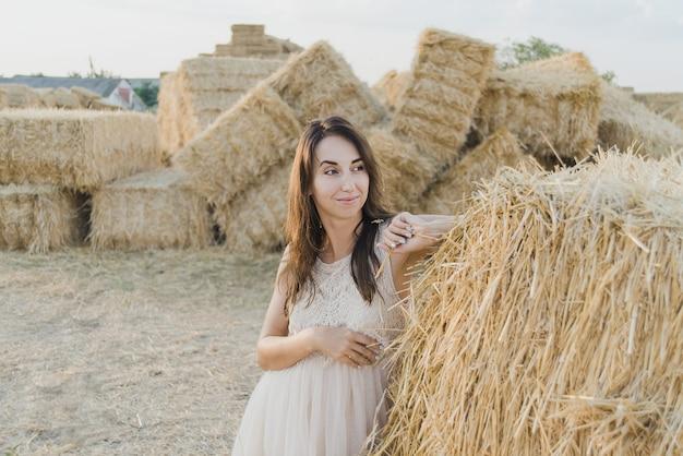 Jong meisje draagt zomer witte jurk in de buurt van hooi baal in veld.